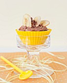 A chocolate cupcake with sliced banana on the top