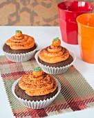 Chocolate cupcakes with pumpkin cream and marzipan pumpkins