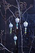 Silberne Walnüsse mit Dekoperlen auf Zweigen als Weihnachtsdeko