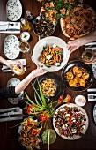 Gedeckter Tisch mit Ravioli, Tomaten-Käse-Salat, Calamari, Pasta Carbonara, Pizza, Conchiglioni Bolognese mit Mozzarella und Muscheln (Italien)