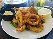A serving of fried calamari rings on a white plate with a lemon and dipping sauce