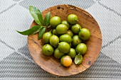 Quenepas (also known as Spanish Limes, genip or Kenips) in a small wodden bowl on a gray surface