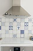 Abzugshaube über Herd mit Abdeckung und weiß-blaue Wandfliesen in der Küche
