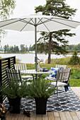 Runder Tisch mit Sonnenschirm und Stühlen auf Terrasse mit Seeblick