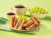 Club sandwich with apple, cheese and chutney, served with grapes and a cup of coffee