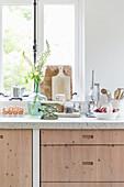 Moderne Landhausküche mit hellen Holzfronten und nostalgischer Deko