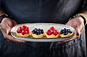 Various berry tarts on an oval dish