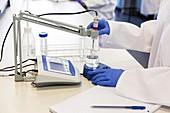Scientist using digital pH meter