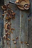 Bucheckern (Fagus sylvatica) in Löffel und auf Holztisch