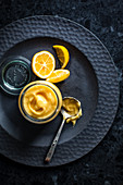 Lemon Curd im Glas auf schwarzem Teller (Draufsicht)