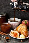 Croissant with jam and butter with coffee being poured