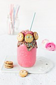 A raspberry and cheesecake smoothie with smiley face cookies