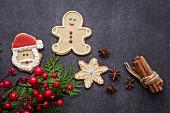 Weihnachtsplätzchen auf Holztisch mit Weihnachtsschmuck und Zimtstangen