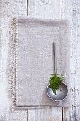 A garlic leaf and flower on a ladle
