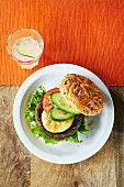 A burger with zucchini, tomato and cucumber