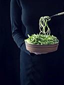 Frau hält Schüssel mit rohen Zucchinispaghetti