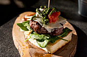A focaccia burger with pecorino, ricotta, pesto, spinach and tomato