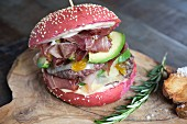 A red burger with beef, ham, avocado, mango and Maltese sauce
