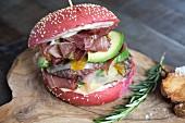 Roter Burger mit Rindfleisch, Schinken, Avocado, Mango und maltesischer Sauce