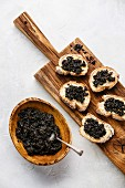 Black caviar in a wooden dish and on slices of white bread