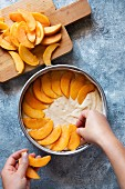 How to make peach cake: top the cake dough with peach wedges