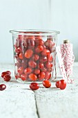 Freshly picked Cornelian cherries in a glass jar on a rustic wooden table