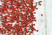 Freshly picked Cornelian cherries scattered on a rustic wooden table