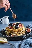 Honey being drizzled over a stack of waffles with berries and figs