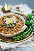 Chana masala on a brass tray with a bunch of fresh coriander (India)