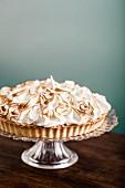 A lemon meringue tart on a cake stand