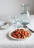 Tomato and watermelon salad on a white tablecloth with a jug and glasses