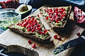Wholegrain bread topped with avocado, pomegranate seeds and sesame
