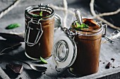 Chocolate pudding decorated with mint leaves and dark chocolate in glass jars