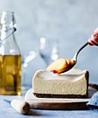 Gluten-free cheesecake being garnished with peach slices