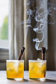 Two Golden Whiskey cocktails with burning cinnamon sticks and ice cubes