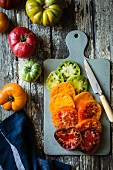 Different-coloured heirloom tomatoes in slices on a chopping board