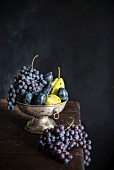 Grapes, plums and pears in a metal bowl on a wooden table