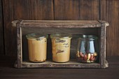 Peanut butter in glasses in front of a wooden background