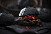 A vegan patty with red chard and salsa in a black burger bun