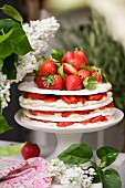 A meringue and cream layered cake with strawberries and basil