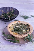 A tartlet with parmesan, wild blueberries and orache