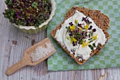 Wholegrain bread with cream cheese, cress and edible flowers