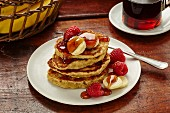 Banana oat pancakes with banana, raspberries and maple syrup (USA)