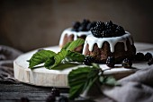 Small vegan ring cakes with icing and fresh blackberries