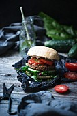A vegan burger with fresh swiss chard and a chia seed bun