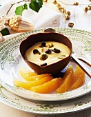 Saffron mousse with pistachios in a chocolate bowl for Christmas