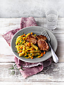 Fried pork medallions with coconut and carrot pasta
