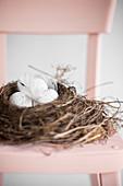 Osternest mit gesprenkelten Eiern auf rosa Stuhl