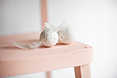 Speckled eggs and feathers on pink chair