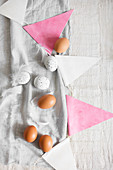 Brown eggs and white, speckled eggs, feathers and bunting